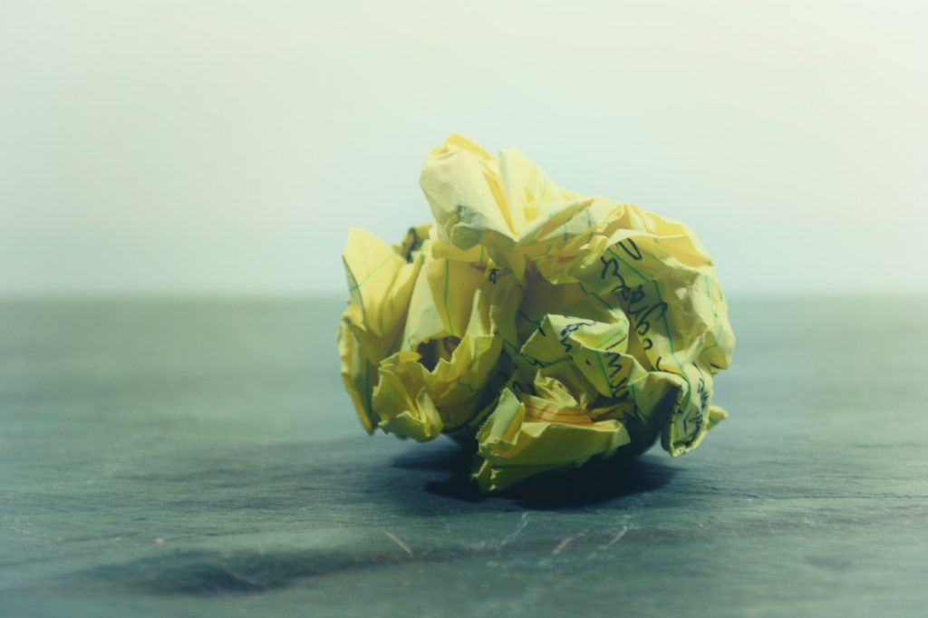 A crumpled yellow, handwritten note on a floor.