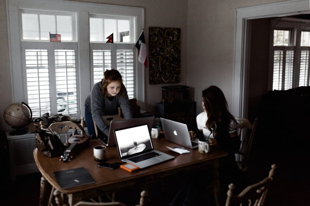 Two women working dedicatedly on laptops on brown wooden table.