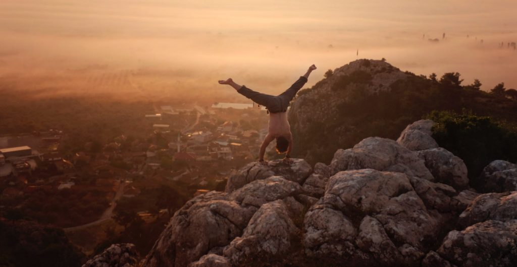 A man doing a handstand on top of a mountain.