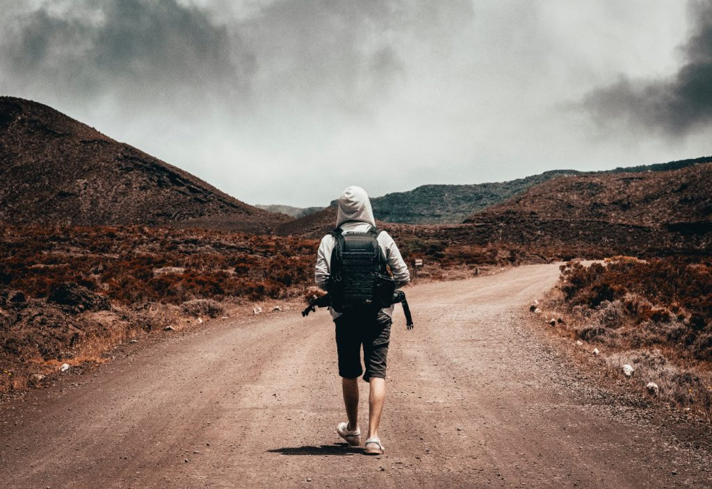 A man carrying a backpack walking on a dusty road.
