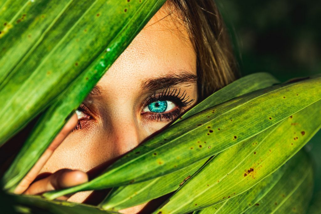 A woman hiding behind green leaves.