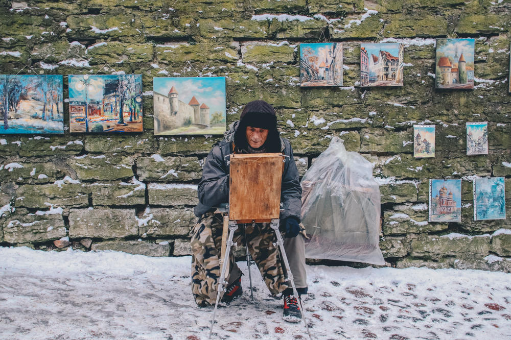 A painter diligently working on a new piece of art on a snowy street in front of a wall full of paintings.