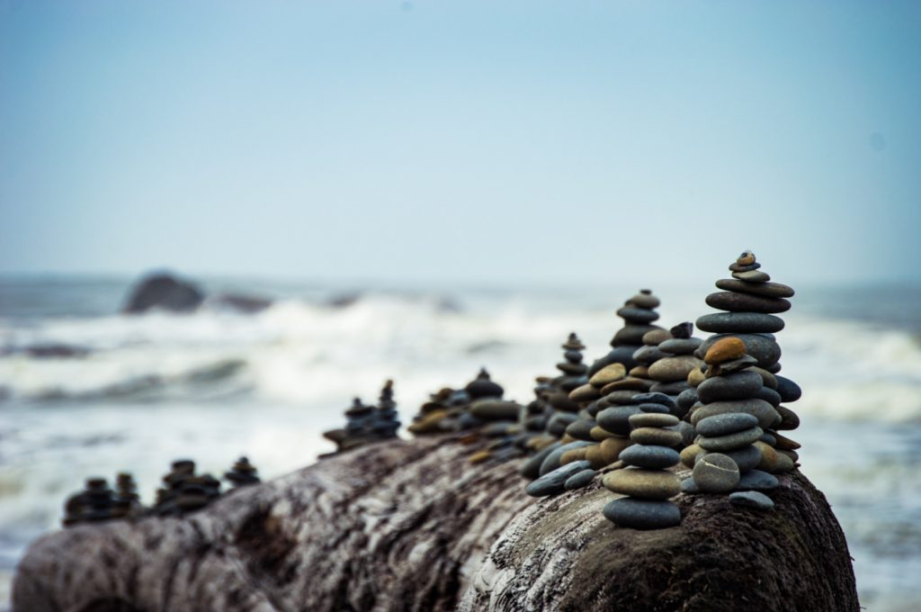 Several intricate pebble piles on a big rock by the sea.