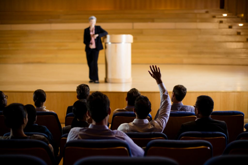 A person in a crowd raising a hand at a lecture.