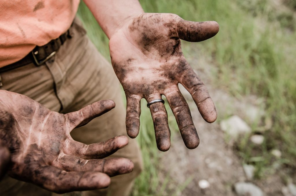 Hands of a man, covered with mud.