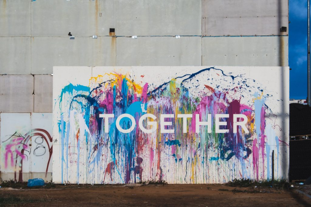 """A word """"together"""" on a colorful mural."""