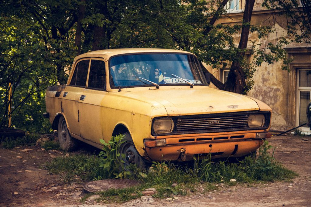 A rusty, old, yellow car in the tall grass.