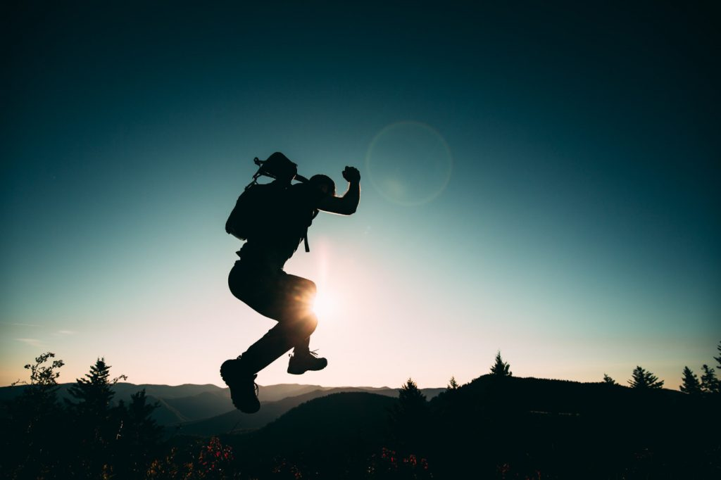 A silhouette of a person jumping on a hill.