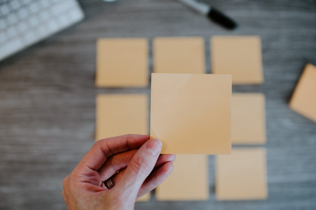 A hand of a person holding a blank sticky note.