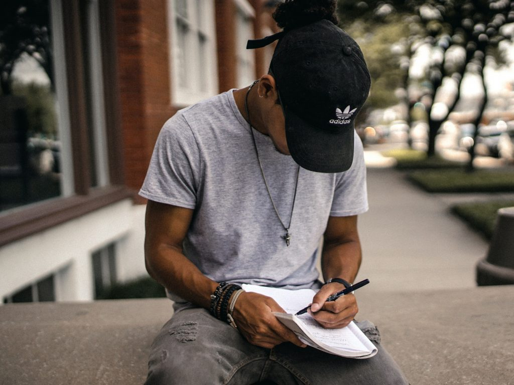 A person sitting on a bench writing in a notebook.