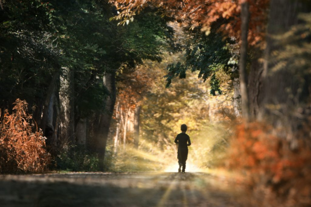 A young boy jogging on the road in the morning.