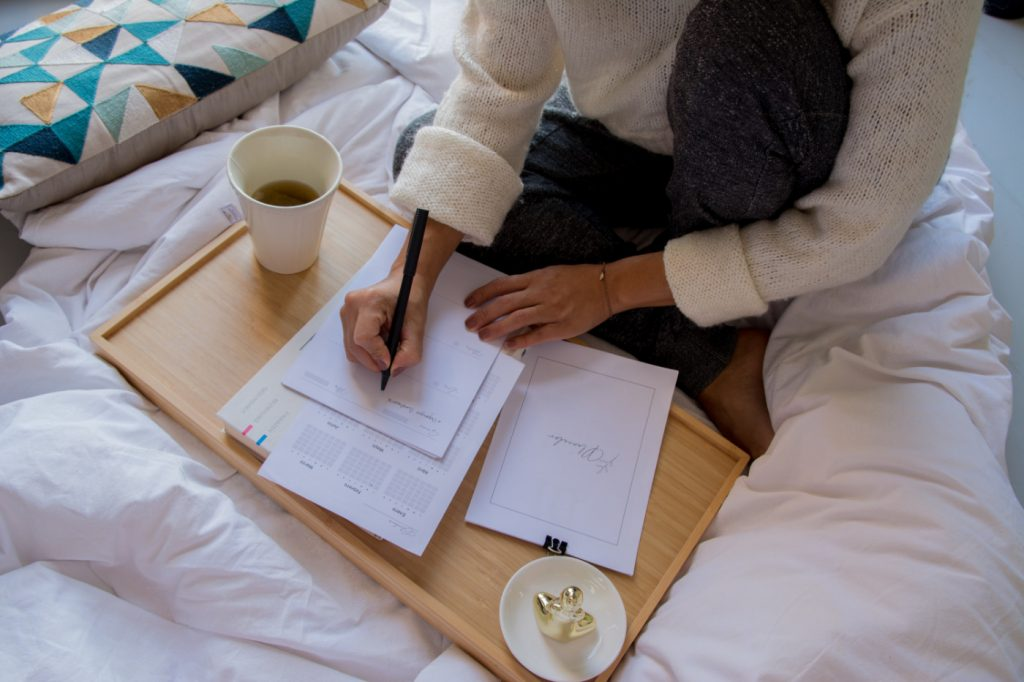 A person holding a pen, reviewing some papers on a wooden table.