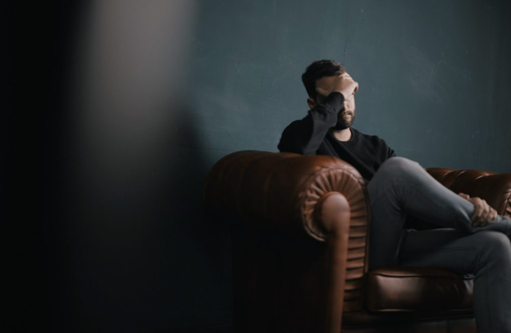 A person sitting on a sofa, holding their head.