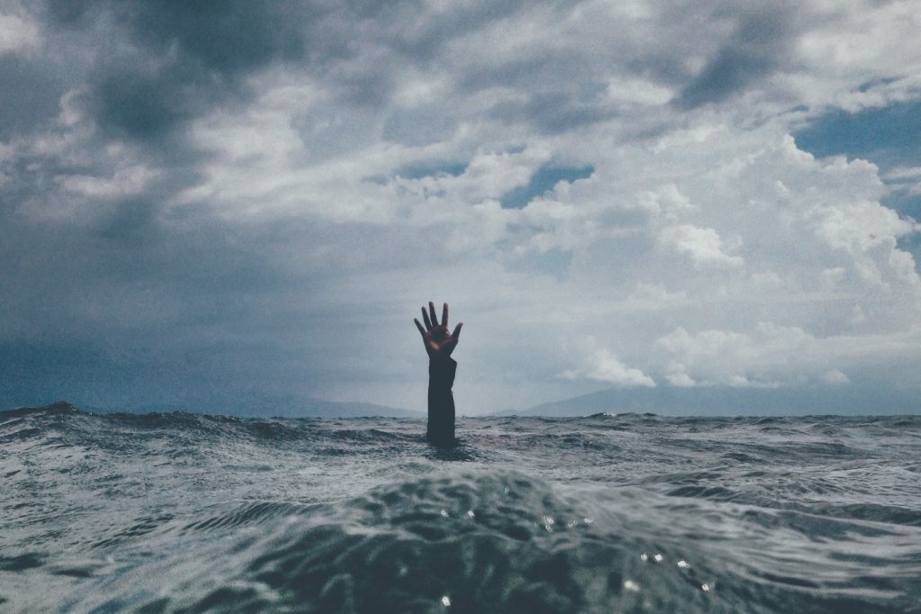 A person's hand reaching out from deep water.