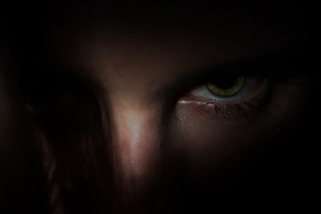 An angry person's face partly in the darkness.