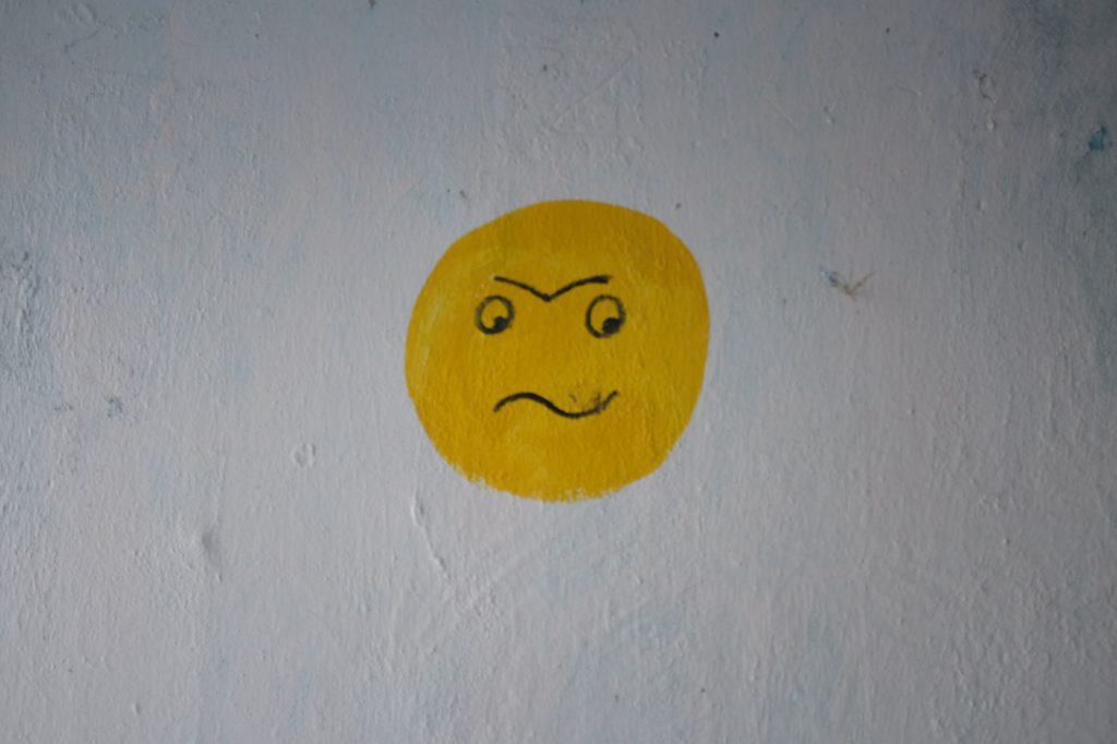 A yellow painting of an angry face resembling an emoji.