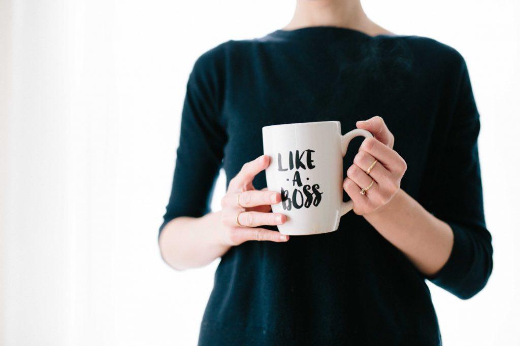 "A woman holding a white mug with ""like a boss"" written on it."