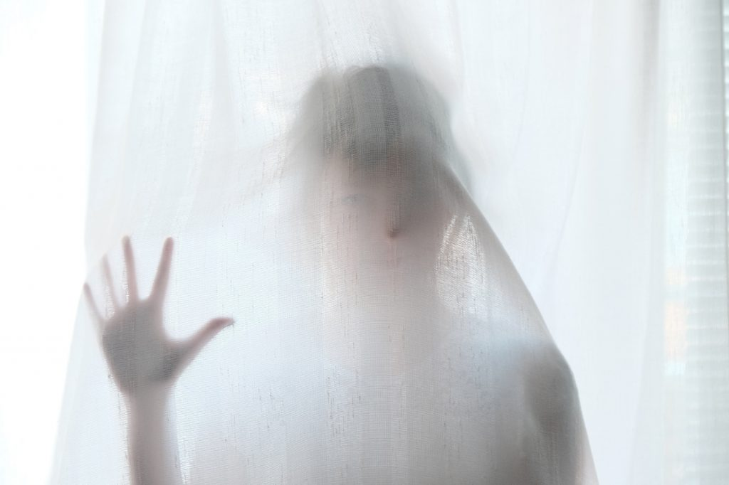 A silhouette of a woman behind a shower curtain.