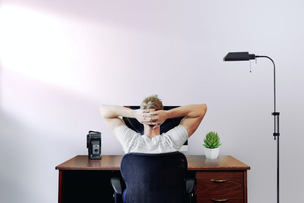 A person holding their head while sitting on a chair at a desk.