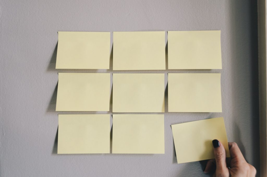 A person tacking one of the six sticky notes from a wall.