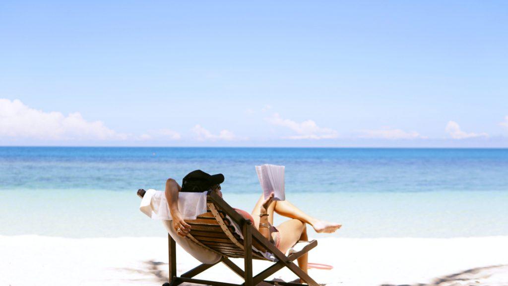 A woman reading on a sunny beach.