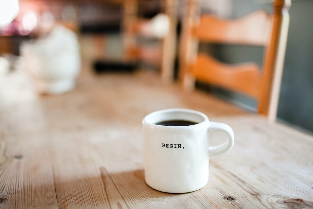 """A cup of coffee on a desk with the word """"begin"""" written on it."""