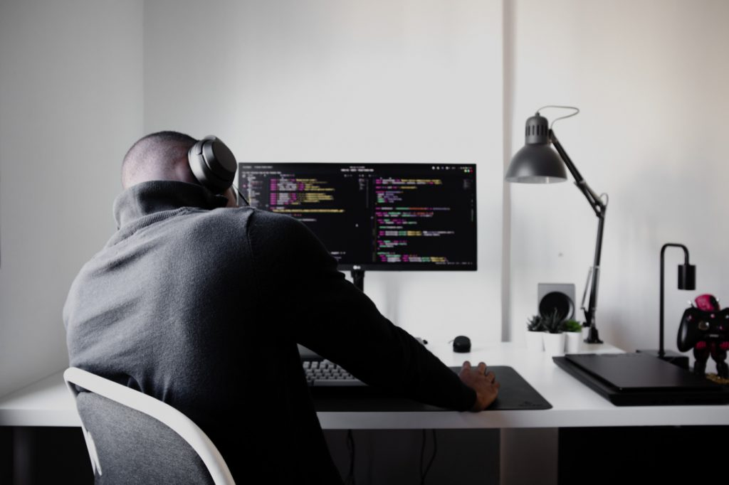 A worried person holding their head sitting on a chair in front of a computer with a code editor opened.