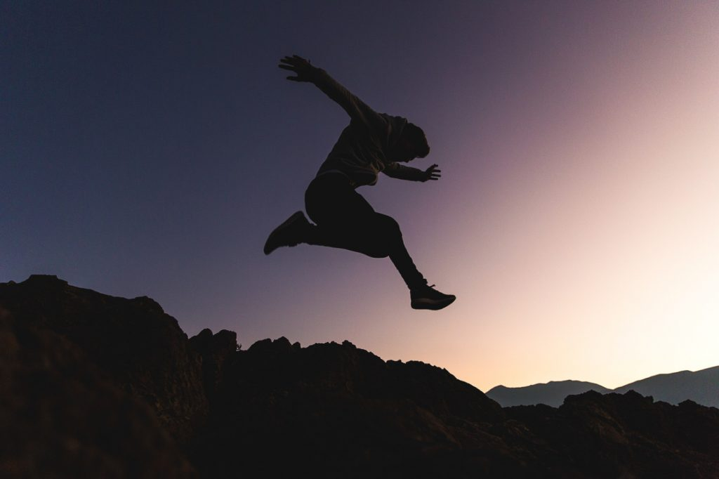 A person jumping above mountains.