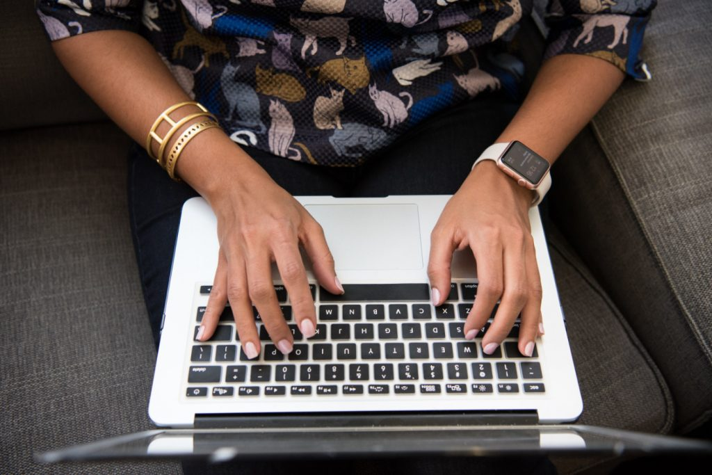 A woman typing on a laptop.