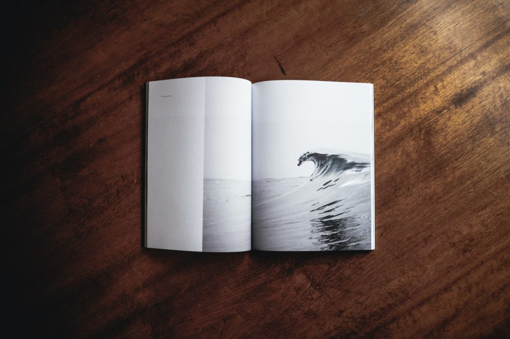 An opened book with a picture of a big wave.