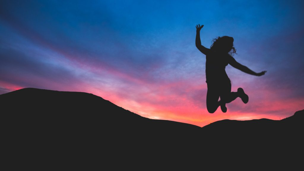 A silhouette of a person jumping in joy.