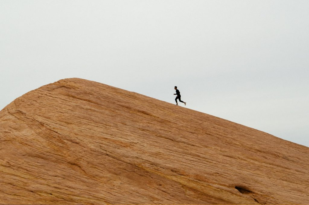 A person running to the top of a hill.