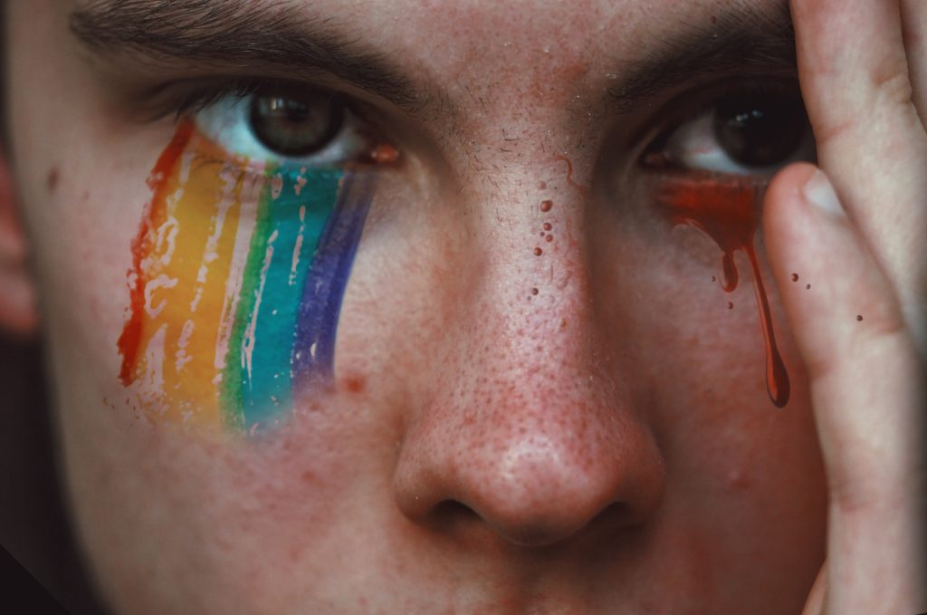 A person with rainbow eyeshadow that looks like tears.