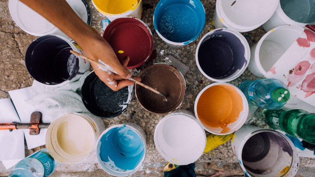 A person dipping a brush into a paint pot among many different colors.