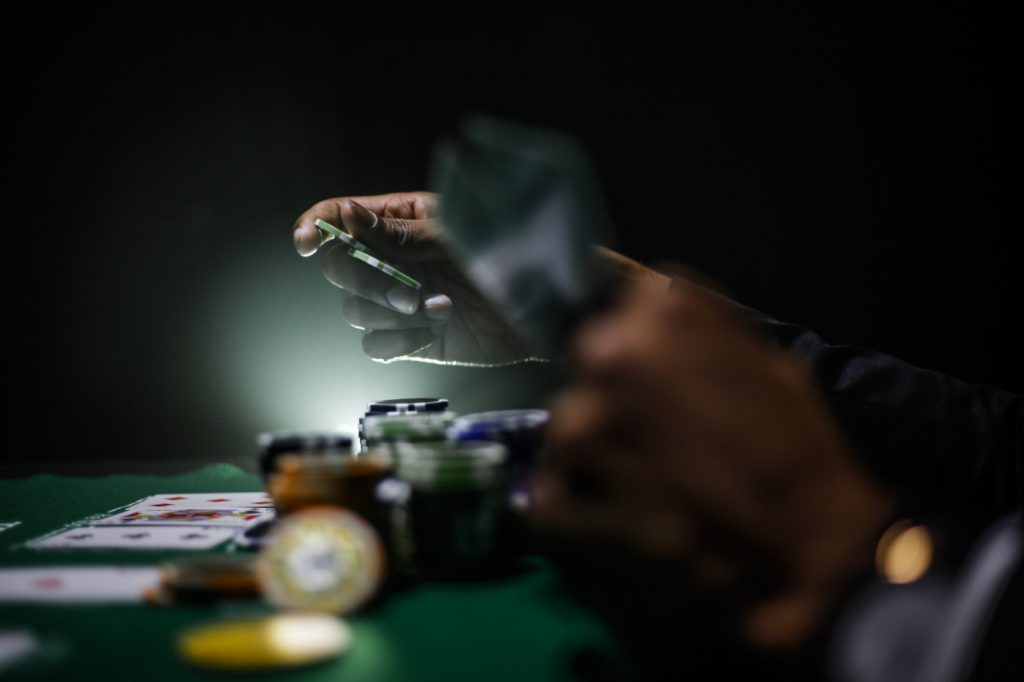 A person holding chips and cards on a poker table.