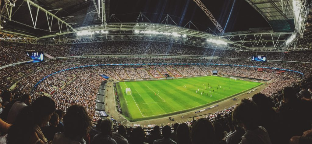 A massive crowd watching a football game in a stadium.