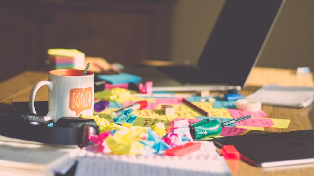 A messy desk with countless sticky notes and random accessories beside an open laptop.