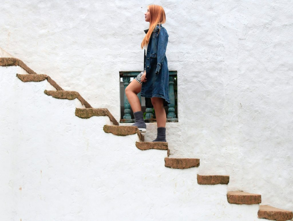 A woman climbing on stairs, looking up.