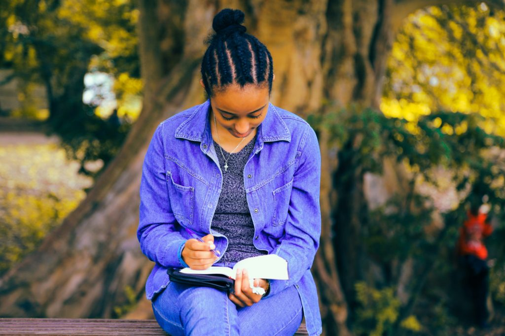 A woman sitting on a bench in a park writing in a notebook.