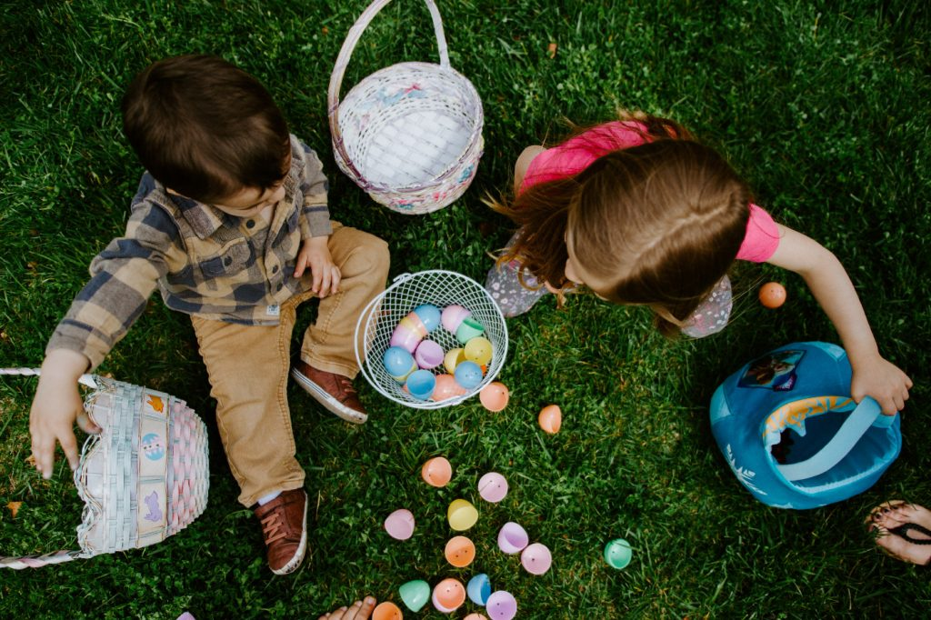 Two children sharing Easter eggs on a green grass field.