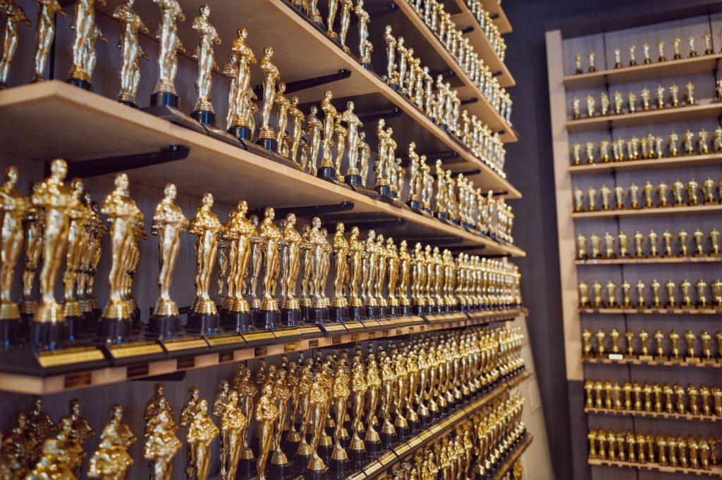 Numerous Oscar awards on shelves.