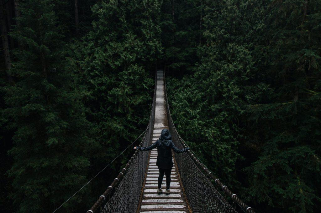 A woman walking across a suspension bridge.