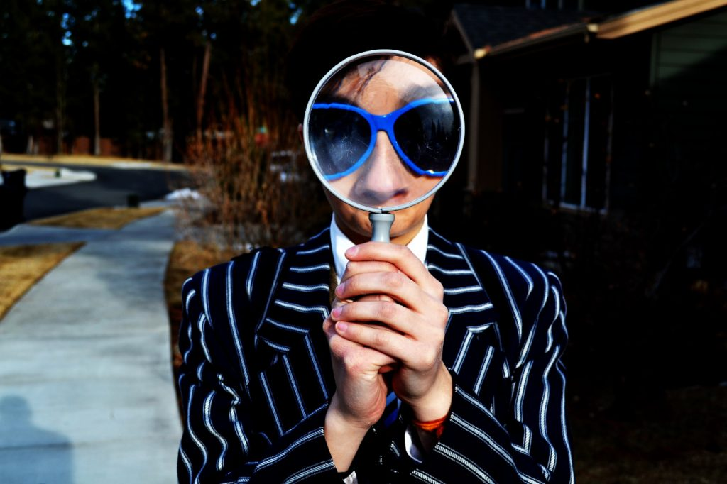 A person holding a magnifying glass enlarging the appearance of their nose and sunglasses.