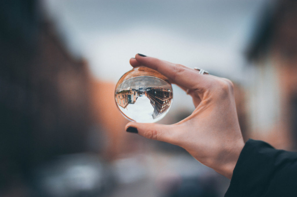 A person holding a clear glass ball through which everything looks upside-down.