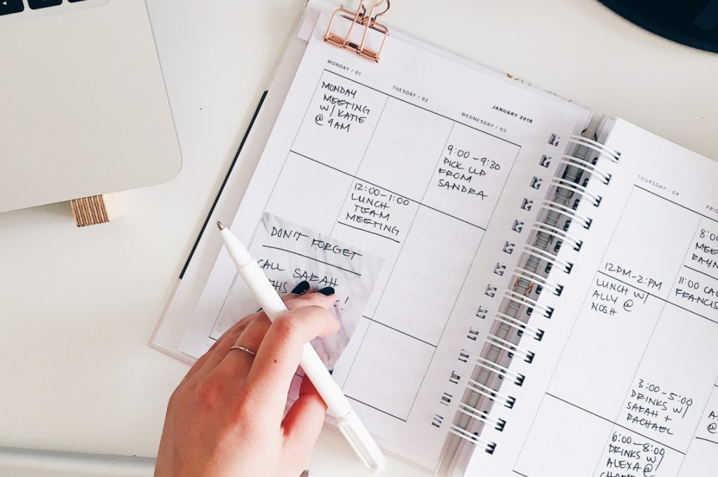 A person holding a pen by an opened planner with a daily schedule.