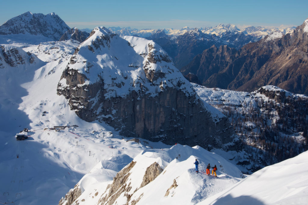 Three people standing on top of a snow-covered mountain.
