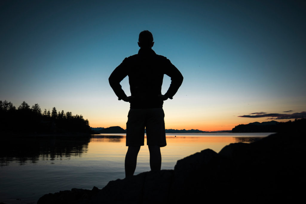 A person standing by a lake in a superhero pose.