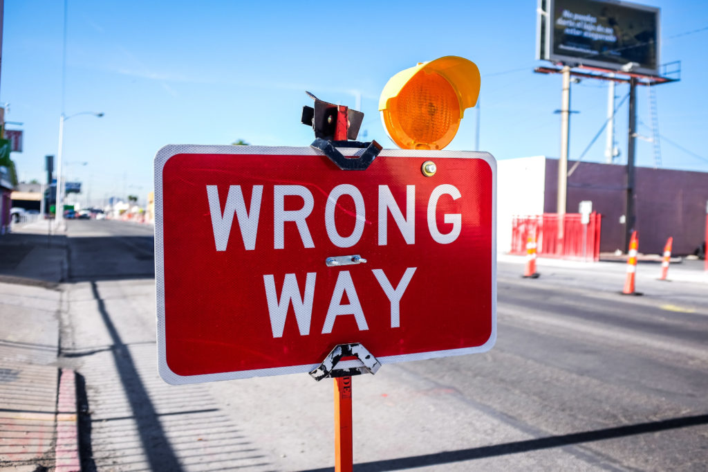 """Red """"Wrong Way"""" sign on the road."""