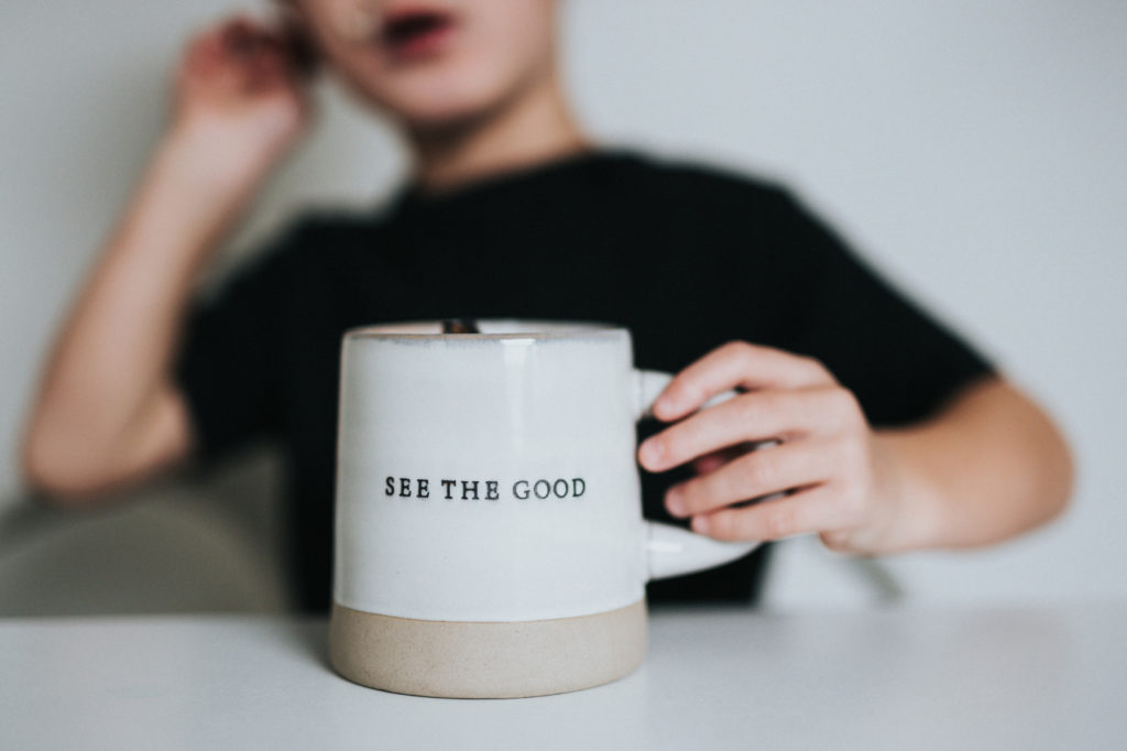 """A person holding a mug with """"see the good"""" written on it."""