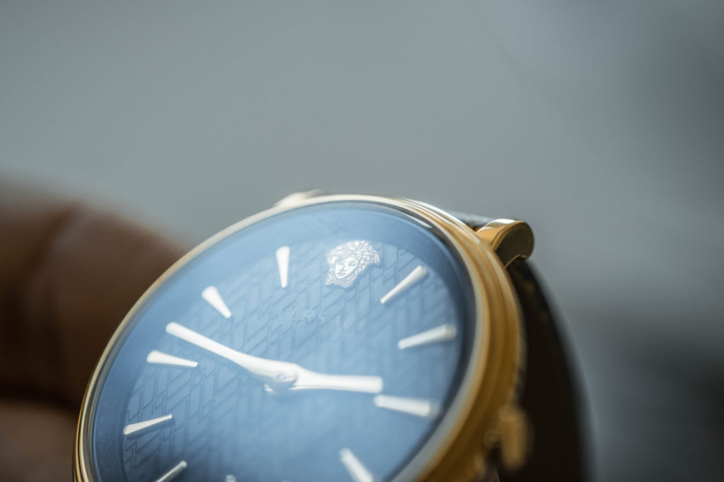 A person holding a wristwatch.